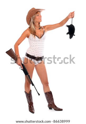 Funny picture of the pretty woman in a cowboy costume with rifle holding big rat.