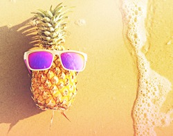 Funny pineapple in sunglasses on the beach.