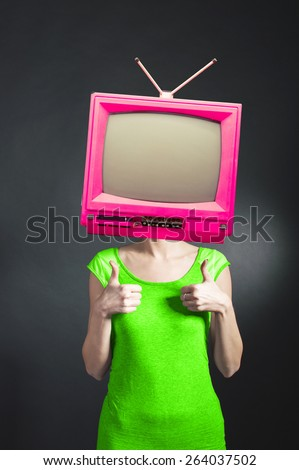 Funny pink TV head young positive crazy woman in green dress posing on isolated black vertical background