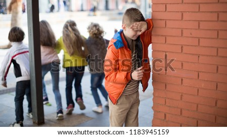 funny playing hide and seek. boy closed eyes his hands standing at brick wall