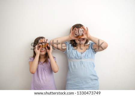 Funny plump girls eat sweet buns on a light background, the concept of unhealthy food, overweight in children