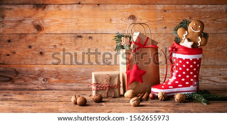 Funny polka dot gumboot as a Santa´s shoe with paper bag, gift boxes, nuts and smiling gingerbread man  on rustic wooden background  -  Christmas decoration  -  Nikolaus  -  Santa Claus boot