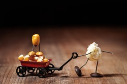 funny popcorn figure is moving a handcart with a corn figure, concepts like Father's Day or playing with the kids