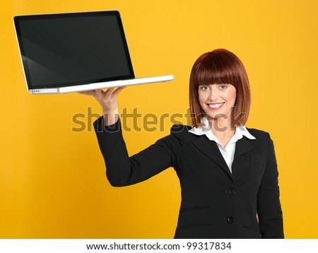 funny portrait of a beautiful, young businesswoman, holding a laptop as a tray, smiling, on yellow background - stock photo