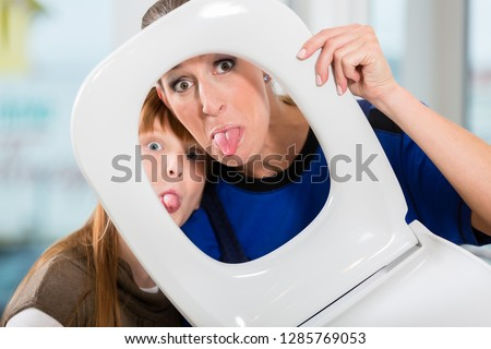 Funny portrait of a cheerful woman and her cute daughter smiling and looking at camera through a white toilet seat in a sanitary ware shop