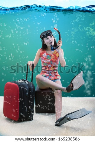 Funny portrait of a girl with her travel luggage and snorkeling equipment sitting under the sea
