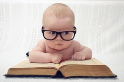 funny portrait of adorable little baby in glasses with old book (thinking expression)