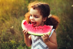 Funny portrait of an incredibly beautiful Red-haired little girl eating watermelon, healthy fruit snack, adorable toddler child with curly hair
