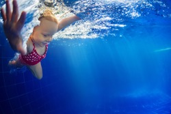 Funny portrait of baby girl swimming and diving in blue pool with fun - jump from poolside deep down underwater with splashes. Family lifestyle and summer children water sports activity with parents.