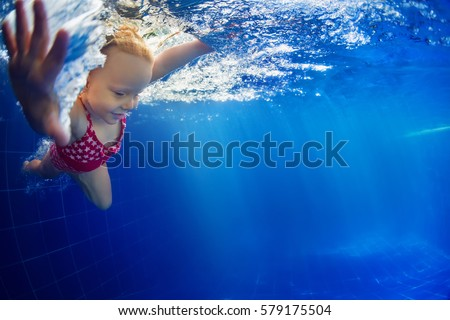Stock Photo Funny portrait of baby girl swimming and diving in blue pool with fun - jump from poolside deep down underwater with splashes. Family lifestyle and summer children water sports activity with parents.