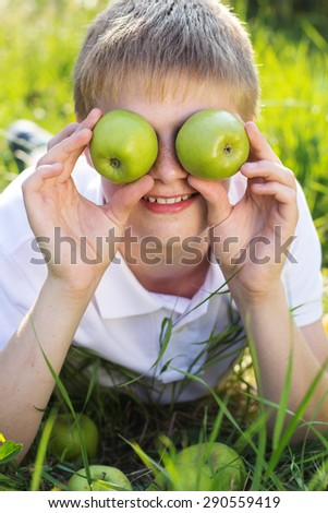Funny portrait of blonde smiling boy with freckle face on his face is holding two green apples