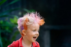 Funny portrait of boy with messy hairstyle. Crazy hipster kid. Stylish boy with painted colorful hair. Happy children having fun and celebrating at party in family summer camp. positive and cheerful.