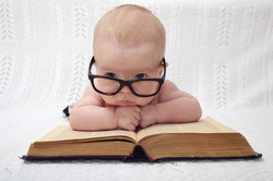 funny portrait of cute  baby in glasses lying over an old big book (vintage style)