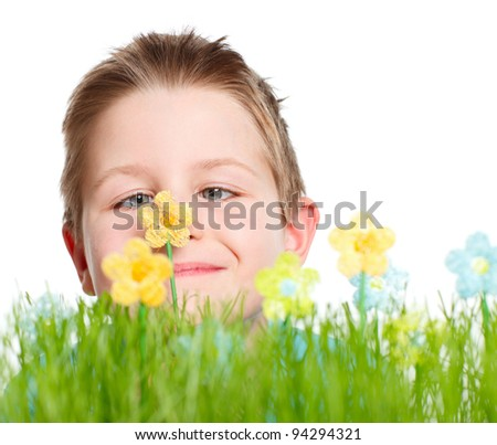 Funny portrait of cute boy looking at flower at middle of his nose