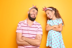 Funny portrait of father and his little daughter on color background