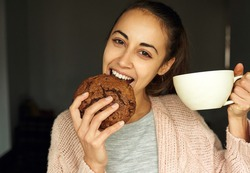 funny portrait of happy young woman with large cup tea, biting huge piece of chocolate cookie and looking at the camera. food, sweets and bakery concept