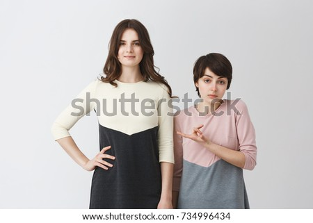 Funny portrait of lesbian pair of young student girls in matching clothes. Long-haired girl being taller than her short girlfriend. Foto stock ©