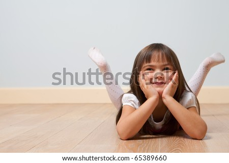 Funny portrait of lying cute girl on a wooden floor indoors