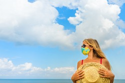 Funny portrait of young woman in straw hat on tropical sea beach. New rules to wear cloth face covering mask at public places due coronavirus COVID 19. Family holiday with kids, travel at summer 2020.