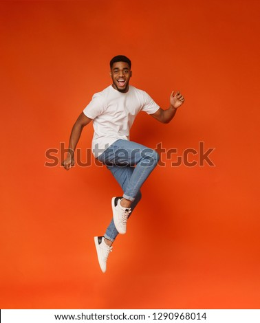 Funny portrait on young african-american man in humorous jump on orange background