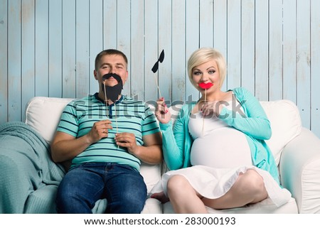 Funny pregnant couple with false mustaches playing at home