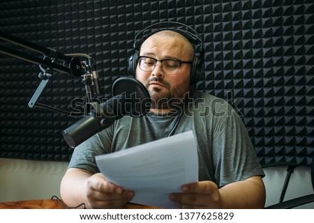 Funny radio presenter or host in radio station studio, portrait of working man