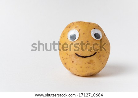 Funny raw potatoes with Googly eyes and smile on white background. Food with funny face.