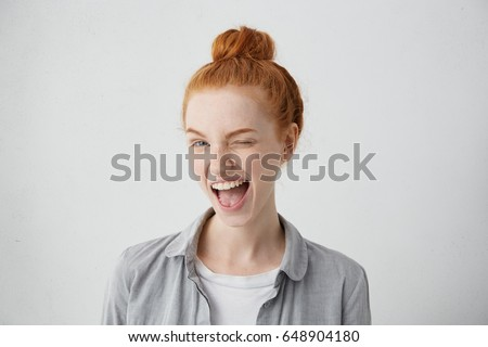 Funny red-haired female teenager with bun wearing casual shirt having joyful expression closing one of her eyes with pleasure and opening widely mouth having broad smile isolated over white background