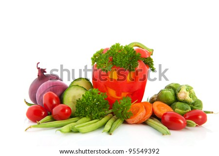 Funny red paprika with smiling face with various vegetables
