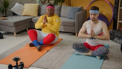 Funny retro fitness couple doing yoga meditation at home. Black overweight man smelling stinky dirty socks screwing up face. Fun, humor, comedy concept.