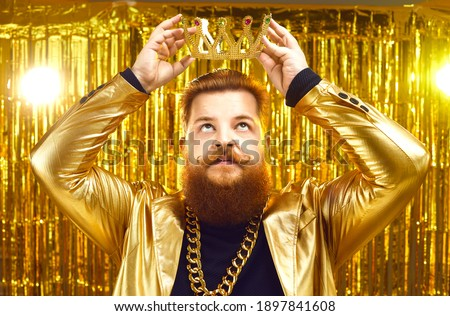 Funny rich young man wearing gold chain and shiny glittering golden jacket putting on king's crown with serious face expression. Ambitious personality, arrogance, megalomania, greed for power concept Stock fotó ©