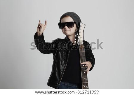 Funny rock child with guitar. fashionable little boy in sunglasses. stylish kid in leather coat. music concept #312711959