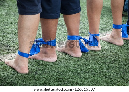 Funny run game, group of sportsmen are tied their legs together and run to finish point