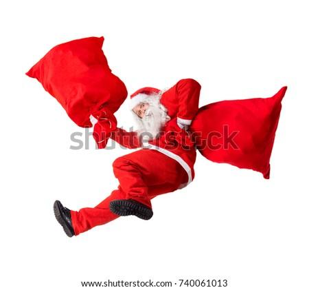 Funny Santa Claus falls with a bag full of x-mas gifts. Santa Claus rushing give gifts at Christmas. Falling Santa carry sack with gift box. - Shutterstock ID 740061013