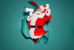 Funny Santa Claus screaming through megaphone, coming out of the green studio background hole.Merry Christmas and Happy New Year concept.