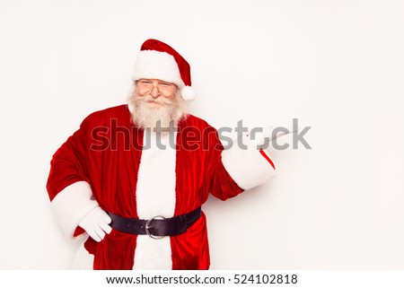 Funny Santa Claus wearing red costume showing something while standing white background