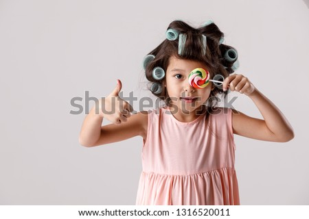 f041b8332 Funny satisfied little child girl in pink dress and hair curlers holding  lollipop on gray background