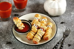 Funny sausage mummies in dough with ketchup for the Halloween party. Children's food.