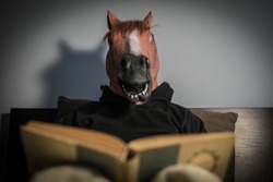 Funny scene with a man with a horse mask trying to read a book and learn