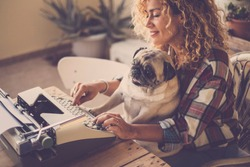 Funny scene with beautiful hipster curly blonde lady working and typing on old typewriter writing a blog or book while her best friend love old dog pug type the same and joke with her owner - together