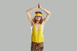 Funny sceptic discontent angry skinny man in glasses, retro yellow headband, tank top and leopard leggings doing yoga exercise looking at camera with suspicious displeased dissatisfied face expression
