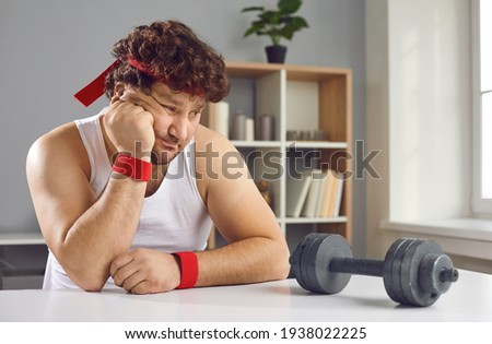 Funny sceptic lazy curly man looking thoughtfully at small barbell unsure whether he needs sports exercise. Sad fat man afraid of failure has no motivation to start training with dumbbells at home Сток-фото ©