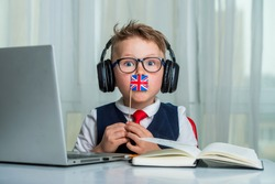 Funny school boy with British flag. Child in headphones and laptop has lesson online