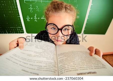 Funny schoolgirl in big round glasses opened the book and stares at the camera. Education.