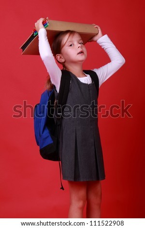 funny schoolgirl with backpack and heavy book