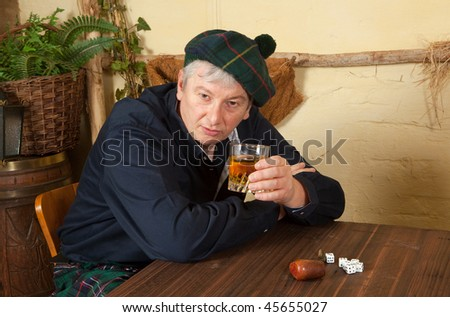 Funny scotsman wearing kilt drinking a glass of whisky in a pub