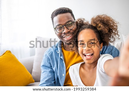 Funny selfie with dad. Self portrait of young father and his little daughter taking selfie while sitting on the floor in bedroom. Family time. Happy father taking selfie with his cute daughter at home