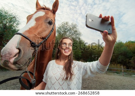 Funny selfie with my friend! Attractive smiling young woman holding smartphone and making selfie with her horse outdoors