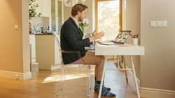 Funny Shot: Businessman Wearing Jacket and No Pants Uses Laptop and Conference Video Call Software App for Board of Directors Online Meeting. Remote Work, Work at Home, Home Office Concept. Side View