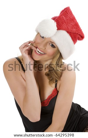 funny shot of a cute blond girl in act to bite her finger wearing a christmas red hat